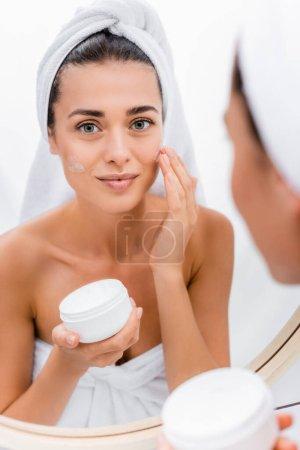 Photo pour Jeune femme avec serviette blanche sur la tête appliquer la crème visage près du miroir dans la salle de bain, avant-plan flou - image libre de droit