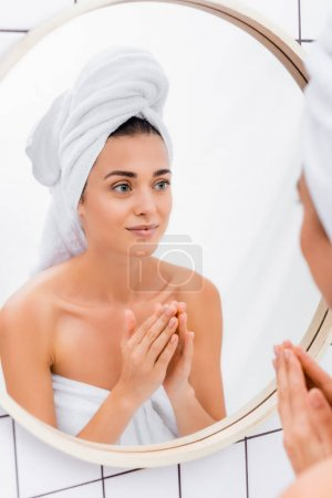woman with towel on head and facial scrub on hands looking in mirror in bathroom, blurred foreground