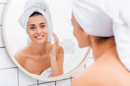 Photo for Cheerful woman applying facial scrub near mirror in bathroom, blurred foreground - Royalty Free Image