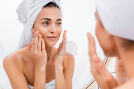 young woman with towel on head applying facial scrub while looking in mirror, blurred foreground