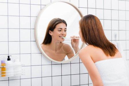 young woman looking in mirror while brushing teeth in bathroom