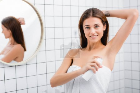 cheerful young woman smiling at camera while using deodorant in bathroom