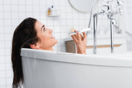 Photo pour Femme gaie parlant sur téléphone portable tout en prenant un bain - image libre de droit
