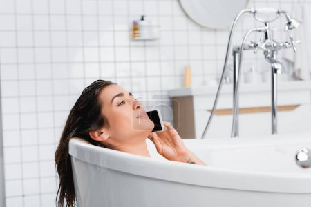 Photo for Young smiling woman taking bath and talking on cellphone - Royalty Free Image