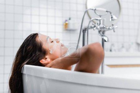 mujer joven en mascarilla relajante con los ojos cerrados en la bañera, fondo borroso