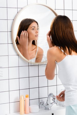 young woman in white singlet looking in mirror in bathroom