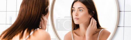 Photo for Young woman with perfect skin looking in mirror in bathroom, blurred foreground, banner - Royalty Free Image