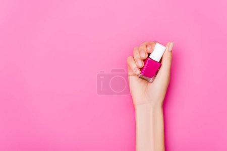 top view of groomed female hand with bottle of glossy nail polish on pink background