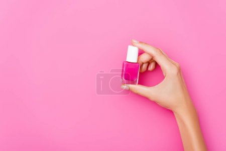top view of groomed female hand with shiny nail polish on pink background