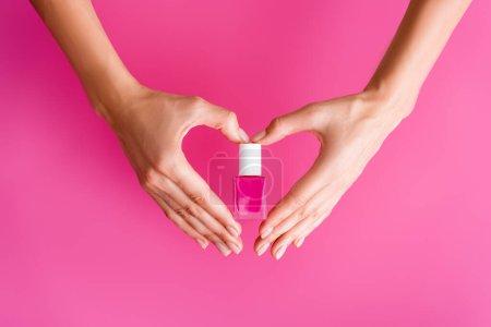 abgeschnittene Ansicht einer Frau, die Herz-Symbol mit Händen macht, während sie eine Flasche Nagellack auf rosa Hintergrund hält