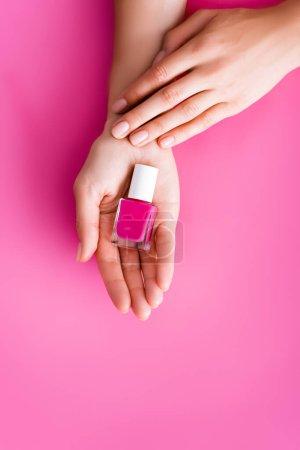 vista recortada de la mujer con botella de barniz de uñas brillante sobre fondo rosa