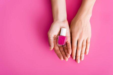 abgeschnittene Ansicht von Frau mit Fläschchen mit glänzendem Nagellack auf rosa Hintergrund