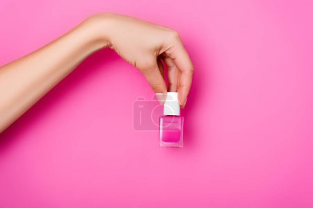 cropped view of woman holding bottle of shiny nail varnish on pink background