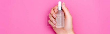 cropped view of woman with bottle of cuticle remover on pink background, banner