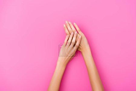 Draufsicht auf gepflegte weibliche Hände mit glänzenden Nägeln auf rosa Hintergrund