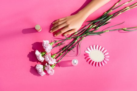 top view of carnation flowers near female hand, palette of artificial nails, nail polish and cuticle remover on pink background