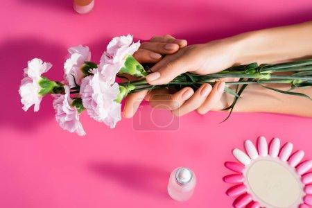 vue recadrée de la femme tenant des fleurs d'oeillet près de la palette de ongles artificiels et décapant de cuticule sur fond rose