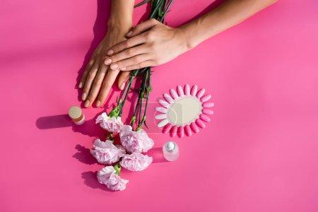 vue de dessus des mains féminines près de la palette de faux ongles, fleurs d'oeillet, et bouteilles de décapant de cuticule et d'émail sur fond rose
