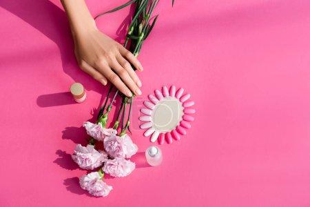 vue du dessus des mains féminines près des bouteilles avec vernis à ongles et décapant pour cuticules, fleurs d'oeillets et palette de faux ongles sur fond rose