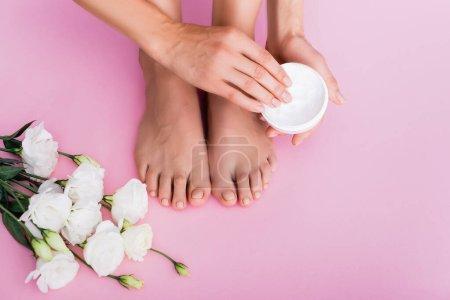 vue recadrée d'une femme pieds nus tenant une crème cosmétique près de fleurs d'eustome blanches sur fond rose