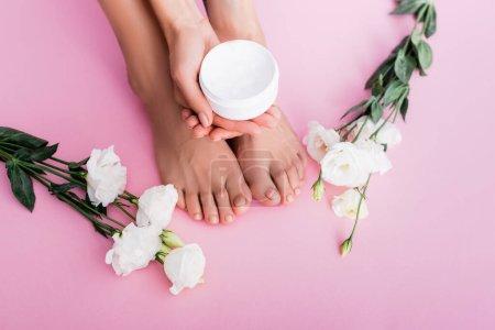 Photo pour Vue recadrée de la femme tenant crème cosmétique près de fleurs d'eustomie blanches sur fond rose - image libre de droit