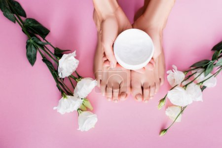 top view of female hands with cosmetic cream near feet and white eustoma flowers on pink background