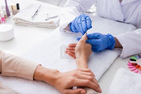 vue partielle du manucure dans les gants en latex à l'aide d'un poussoir à cuticule tout en faisant la manucure au client