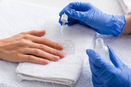 partial view of manicurist applying cuticle remover while making manicure to client