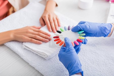 partial view of manicurist showing palette of fake nails to client on blurred background