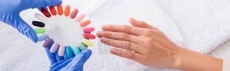 Teilansicht der Maniküre, die eine Reihe von bunten falschen Nägeln in der Nähe der Hand des Kunden hält, Banner