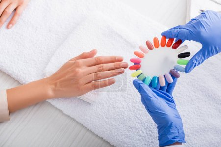 partial view of manicurist holding samples of colorful artificial nails near hand of client