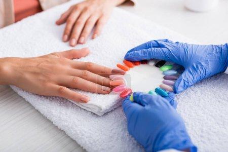 vista recortada de manicura celebración conjunto de uñas artificiales multicolores cerca de la mano del cliente, fondo borroso