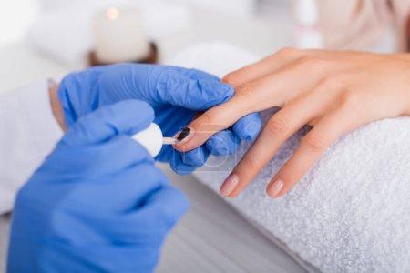 vista recortada de la manicura aplicando barniz de uñas en la uña del cliente, borrosa primer plano