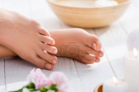 Photo pour Vue recadrée des pieds féminins avec pédicure rose pastel sur la surface en bois blanc, avant-plan flou - image libre de droit