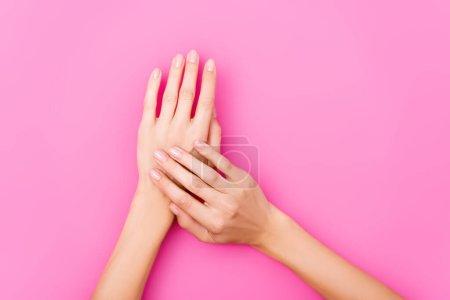 vista superior de las manos femeninas con esmalte de uñas pastel en las uñas sobre fondo rosa