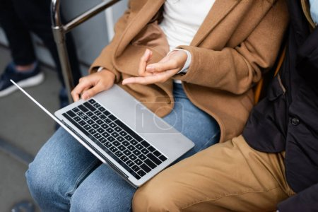 cropped view of african american woman pointing with finger at laptop near man in subway