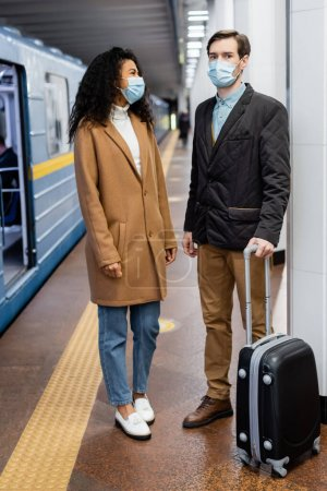 interracial couple in medical masks standing on platform with luggage