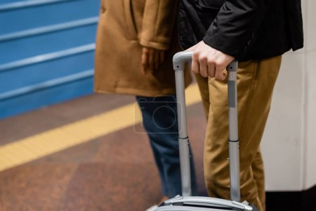 partial view of couple standing on platform of subway with luggage