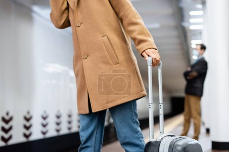 cropped view of woman standing with baggage near blurred man in subway