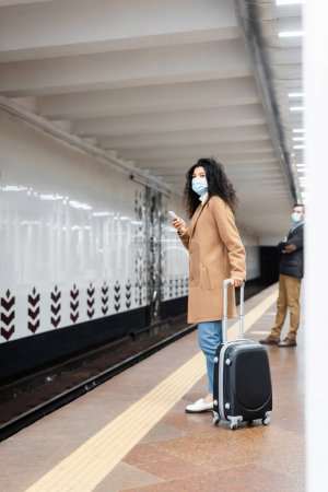 full length of african american woman in medical mask standing with luggage near man in subway