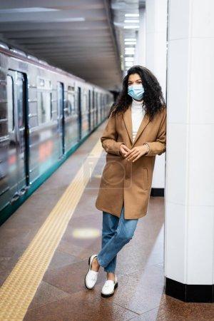 Photo pour Pleine longueur de frisée afro-américaine en masque médical debout dans le métro - image libre de droit