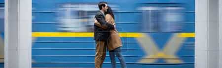 motion blur of interactional couple hugging near wagon in subway, banner
