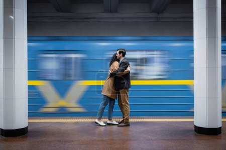 motion blur of interactional couple hugging near wagon in subway
