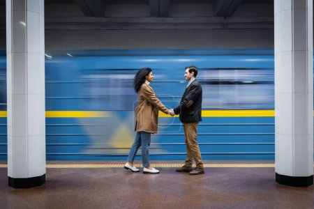 long exposure of interactional couple holding hands while standing near wagon in subway