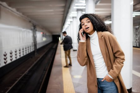 surprised african american woman talking on smartphone and looking away in subway on blurred background