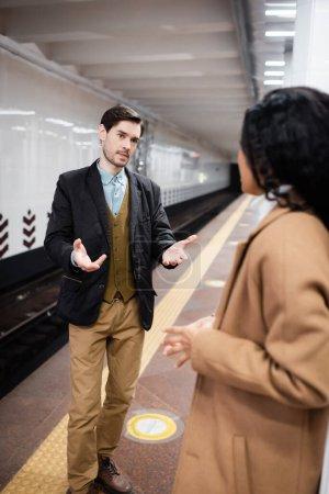 Photo pour Homme geste tout en parlant avec afro-américaine femme sur fond flou - image libre de droit