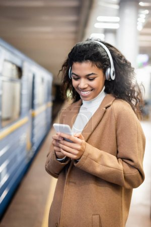 smiling african american woman in wireless headphones using smartphone while listening music in subway