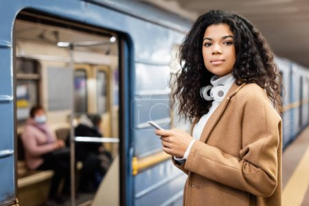 smiling african american woman in wireless headphones holding smartphone in subway