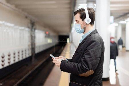 Photo pour Vue latérale de l'homme tatoué en masque médical et écouteurs sans fil tenant smartphone dans le métro - image libre de droit