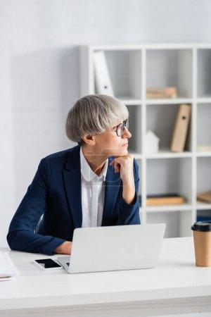 Photo pour Cher chef d'équipe dans les lunettes regardant loin près des gadgets et du café pour aller sur le bureau - image libre de droit